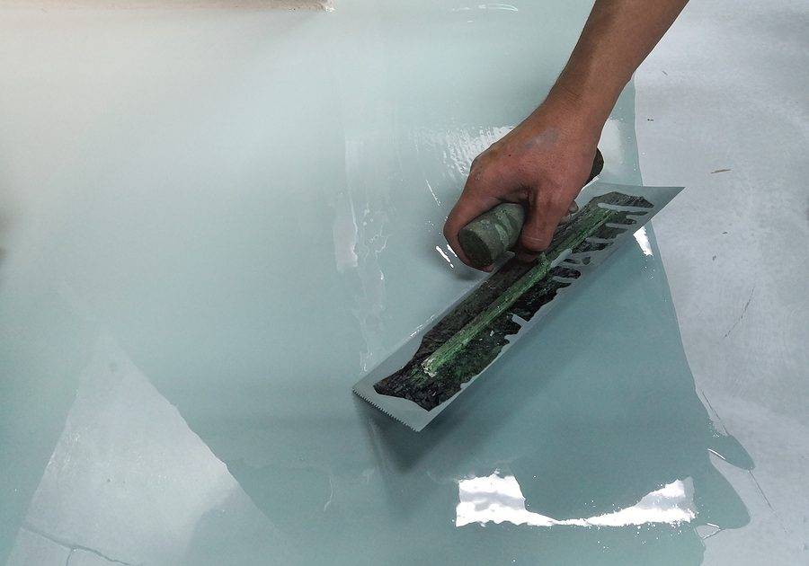 construction workers are painting the floor using the method self-leveling epoxy. spreading self leveling compound with trowel.
